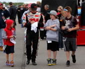 Greg Biffle driver of the 3M Ford signs autographs in the garage area during practice for the NASCAR Sprint Cup Series Party in the Poconos 400 at...