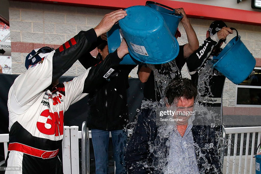 Greg Biffle, driver of the #16 3M Hire Our Heroes Ford, Danica Patrick, driver of the #10 GoDaddy Chevrolet, Jamie McMurray, driver of the #1 McDonald's Chevrolet, and Jimmie Johnson, driver of the #48 Lowe's Chevrolet, assist NASCAR president Mike Helton in the ice bucket challenge after qualifying for the NASCAR Sprint Cup Series Irwin Tools Night Race at Bristol Motor Speedway on August 22, 2014 in Bristol, Tennessee. The drivers donated $1,000.00 each to participate in the challenge.