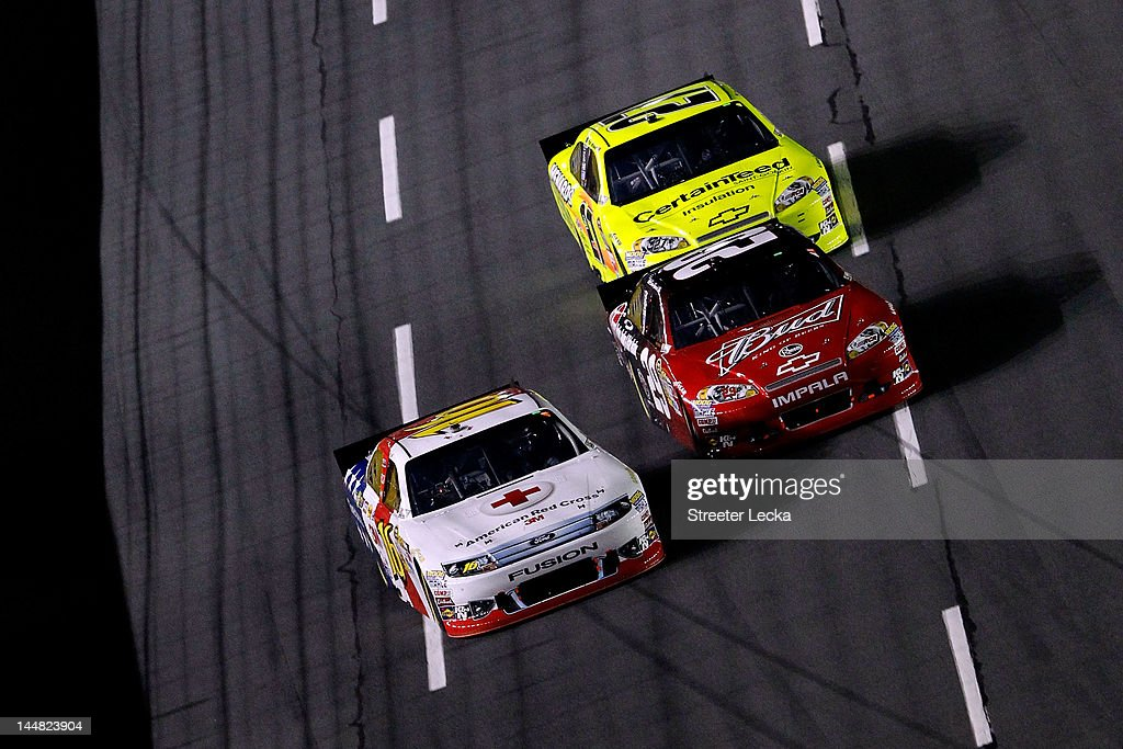 Greg Biffle, driver of the #16 3M/American Red Cross Ford, leads Kevin Harvick, driver of the #29 Budweiser/Rheem Chevrolet, and Paul Menard, driver of the #27 Menards/CertainTeed Chevrolet,during the NASCAR Sprint All-Star Race at Charlotte Motor Speedway on May 19, 2012 in Charlotte, North Carolina.