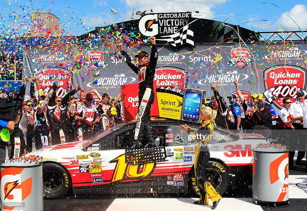 Greg Biffle driver of the 3M/Give Kids a Smile Ford celebrates in Victory Lane after winning the NASCAR Sprint Cup Series Quicken Loans 400 at...