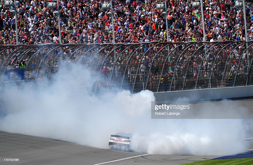 Greg Biffle, driver of the #16 3M/Give Kids a Smile Ford, celebrates with a burnout after winning the NASCAR Sprint Cup Series Quicken Loans 400 at Michigan International Speedway on June 16, 2013 in Brooklyn, Michigan.