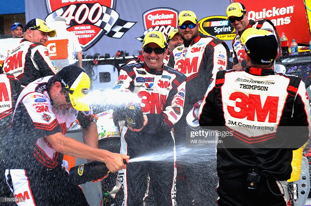 Greg Biffle, driver of the #16 3M/Give Kids a Smile Ford, celebrates with teammates in Victory Lane after winning the NASCAR Sprint Cup Series Quicken Loans 400 at Michigan International Speedway on June 16, 2013 in Brooklyn, Michigan.