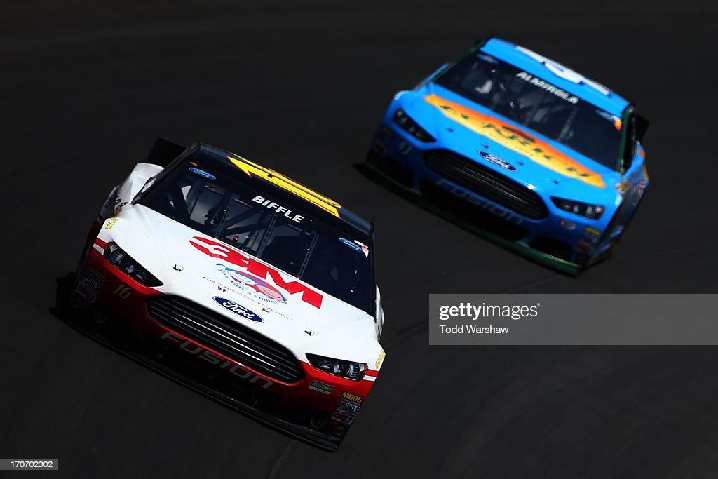 Greg Biffle, driver of the #16 3M/Give Kids a Smile Ford, races Aric Almirola, driver of the #43 Eckrich Ford, during the NASCAR Sprint Cup Series Quicken Loans 400 at Michigan International Speedway on June 16, 2013 in Brooklyn, Michigan.