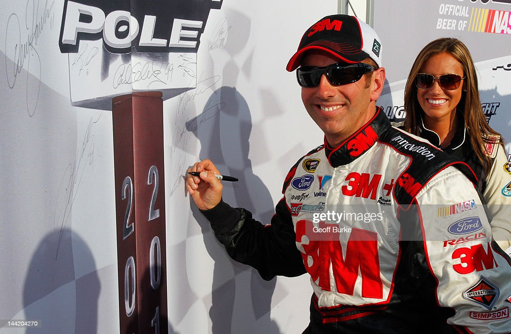 <a gi-track='captionPersonalityLinkClicked' href=/galleries/search?phrase=Greg+Biffle&family=editorial&specificpeople=209093 ng-click='$event.stopPropagation()'>Greg Biffle</a>, driver of the #16 3M/OH/ES Ford, signs the Coors Light Pole Award board as Miss Coors Light Rachel Rupert looks on after qualifying for pole position for the NASCAR Sprint Cup Series Bojangles' Southern 500 at Darlington Raceway on May 11, 2012 in Darlington, South Carolina.