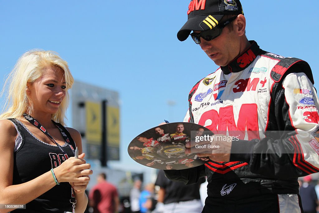 Greg Biffle, driver of the #16 Post-it Ford, signs an autograph for a fan in the garage prior to practice for the NASCAR Sprint Cup Series Geico 400 at Chicagoland Speedway on September 14, 2013 in Joliet, Illinois.