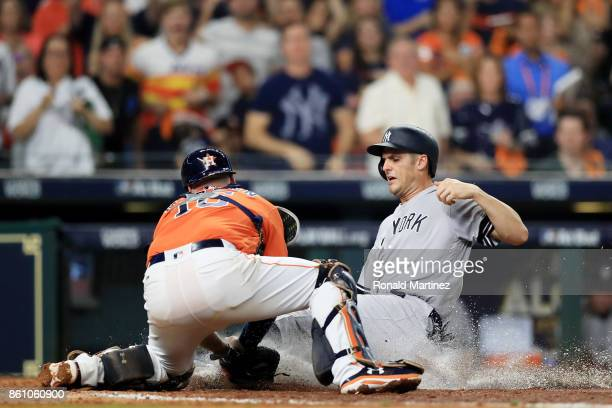 Greg Bird of the New York Yankees is tagged out at home by Brian McCann of the Houston Astros in the fifth inning during game one of the American...