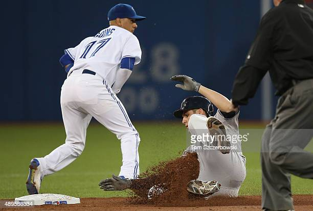 Greg Bird of the New York Yankees slides safely into second base with a double in the first inning during MLB game action against the Toronto Blue...