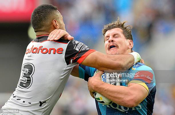 Greg Bird of the Titans is hit high in the tackle by David Fusitu'a of the Warriors during the round 22 NRL match between the Gold Coast Titans and...