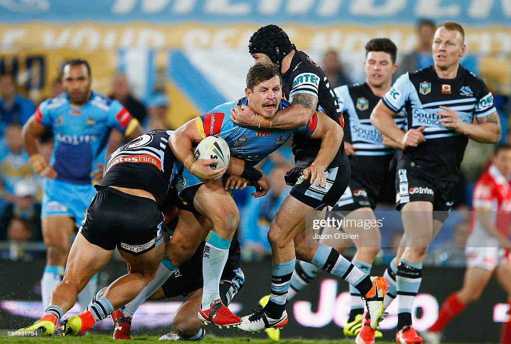 Greg Bird of the Titans is tackled by Michael Ennis of the Sharks during the round 21 NRL match between the Gold Coast Titans and the Cronulla Sharks at Cbus Super Stadium on August 1, 2016 in Gold Coast, Australia.