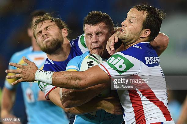 Greg Bird of the Titans is tackled by Robbie Rochow and Tyrone Roberts of the Knights during the round three NRL match between the Gold Coast Titans...