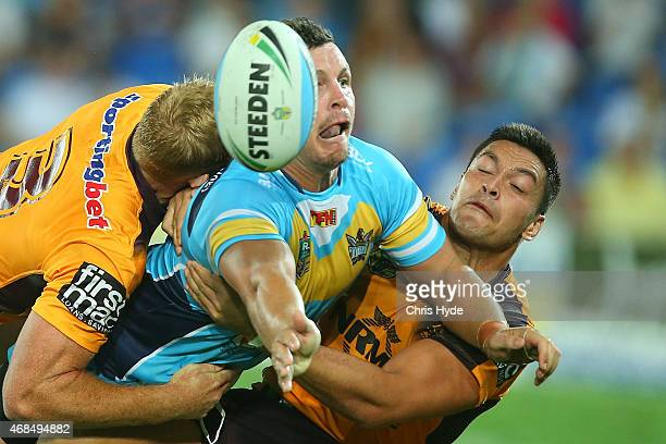 Greg Bird of the Titans offloads while tackled during the round five NRL match between the Gold Coast Titans and the Brisbane Broncos at Cbus Super...