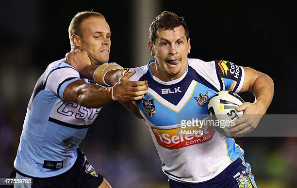 Greg Bird of the Titans puts a fend on Daniel Holdsworth of the Sharks during the round one NRL match between the Cronulla Sharks and the Gold Coast...