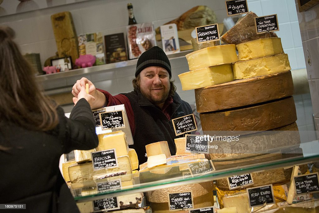 Greg Blais, a cheese monger, hands a customer a sample of cheese at an Eataly location in the Flatiron district of New York, U.S., on Wednesday, Feb. 6, 2013. Eataly is a high-end Italian food market/mall chain, owned by a partnership including Mario Batali, Lidia Bastianich and Joe Bastianich, which first opened in Turin, Italy, in 2007. Photographer: Scott Eells/Bloomberg via Getty Images
