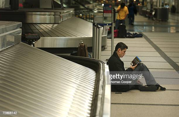 Greg Brown of Bay City Texas sits and reads a book next to a baggage carousel at Denver International Airport on December 22 2006 in Denver Colorado...