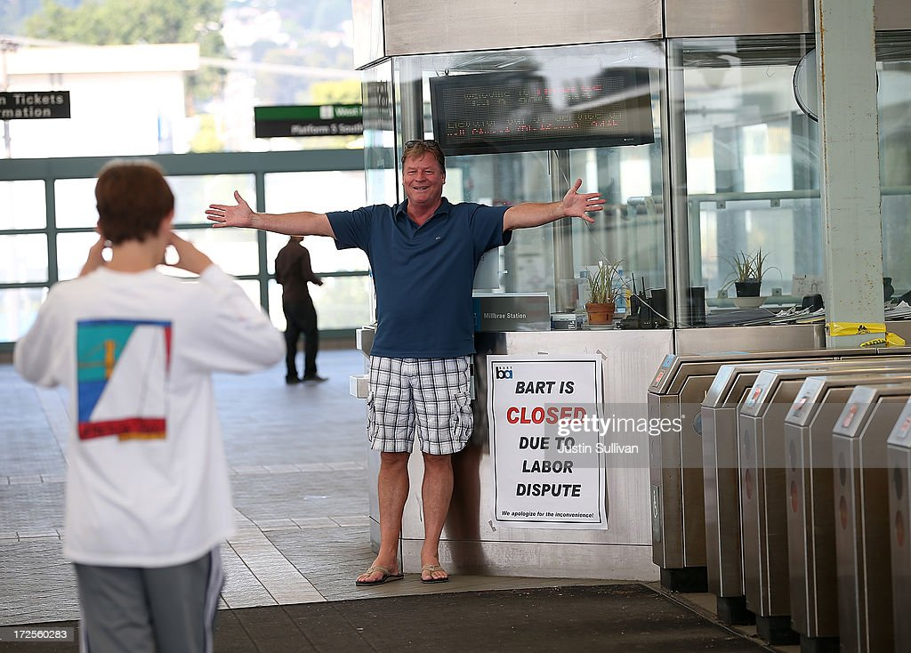 Greg Burrell (R) from Florida, has his son Ben Burrell (L) take a picture of him in front of a closure sign at the Bay Area Rapid Transit (BART) Millbrae station on July 3, 2013 in Millbrae, California. For a third day, hundreds of thousands of San Francisco Bay Area commuters are scrambling to find ways to work as two of San Francisco Bay Area Rapid Transit's (BART) largest unions remain on strike while they continue contract negotiations with management. Train operators, mechanics, station agents and maintenance workers are seeking a five percent wage increase and are fighting management who want to have workers to begin contributing to their pensions, pay more for health insurance and reduce overtime expenses.