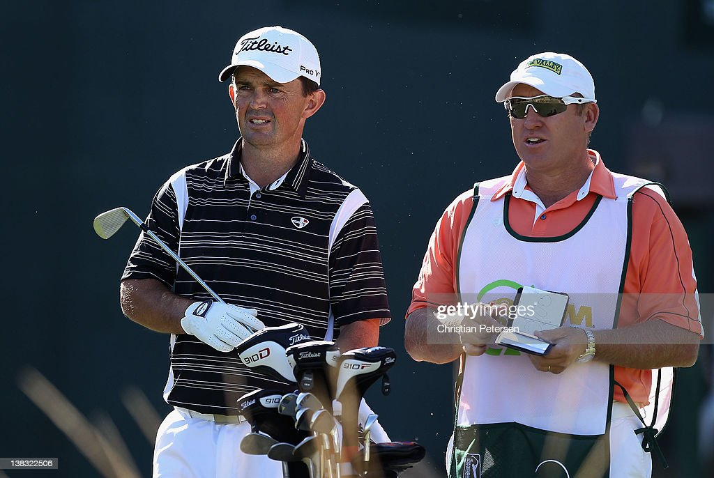 Greg Chalmers of Australia stands with his caddie before hitting a tee shot on the 16th hole during the final round of the Waste Management Phoenix Open at TPC Scottsdale on February 5, 2012 in Scottsdale, Arizona.