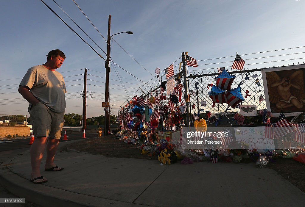 Greg Danielson of Prescott looks over the makeshift memorial outside of Station 7 on July 3, 2013 in Prescott, Arizona. Nineteen firefighters based out of Station 7 died battling a fast-moving wildfire near Yarnell, Arizona on June 30. Station 7 has been the home of the Granite Mountain Interagency Hotshot Crew since 2010.
