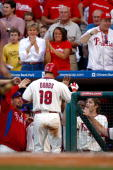 Greg Dobbs of the Philadelphia Phillies celebrates with teammates in the dugout after scoring on a RBI double by Carlos Ruiz in the bottom of the...