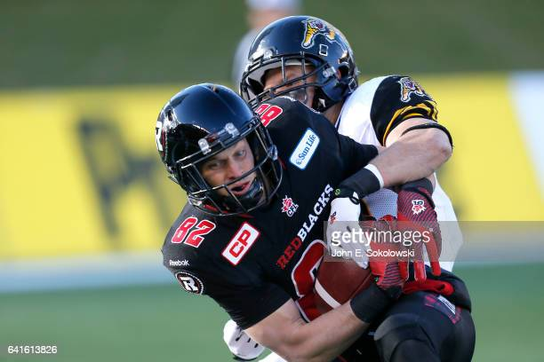 Greg Ellingson of the Ottawa REDBLACKS makes a catch against Erik Harris of the Hamilton TigerCats during the CFL Eastern Final Playoff game at TD...