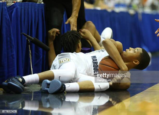 Greg Elliott of the Marquette Golden Eagles and Wayde Sims of the LSU Tigers go to the floor chasing a loose ball during the first half of their game...