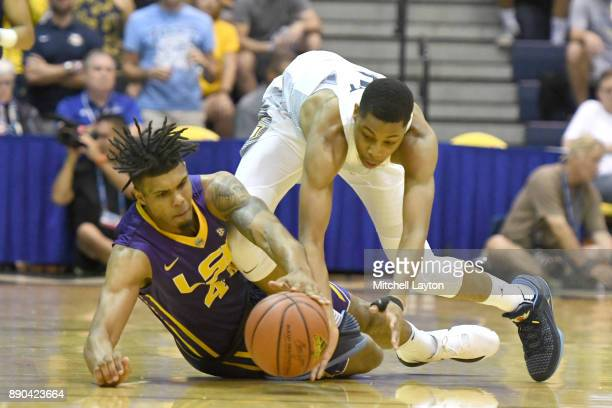 Greg Elliott of the Marquette Golden Eagles and Wayde Sims of the LSU Tigers fight for a loose ball during a consultation college basketball game at...