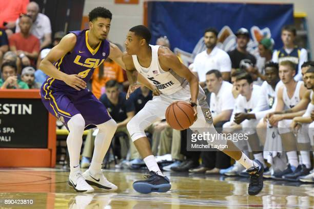 Greg Elliott of the Marquette Golden Eagles dribbles the ball by Skylar Mays of the LSU Tigers during a consultation college basketball game at the...