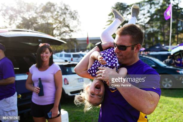 Greg Evans flips his daughter Brinkley Evans 3yearsold both of Merry Hill North Carolina tailgating before the game as the East Carolina Pirates host...