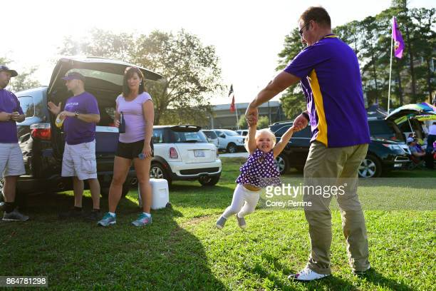 Greg Evans spins his daughter Brinkley Evans 3yearsold both of Merry Hill North Carolina tailgating before the game as the East Carolina Pirates host...