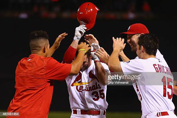 Greg Garcia of the St Louis Cardinals is congratulated by teammates after drawing a walkoff walk against the Colorado Rockies in the ninth inning at...