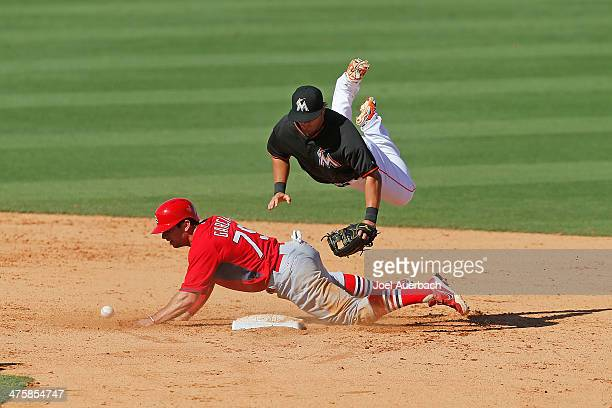 Greg Garcia of the St Louis Cardinals takes out Avery Romero of the Miami Marlins in the seventh inning during a spring training game at Roger Dean...