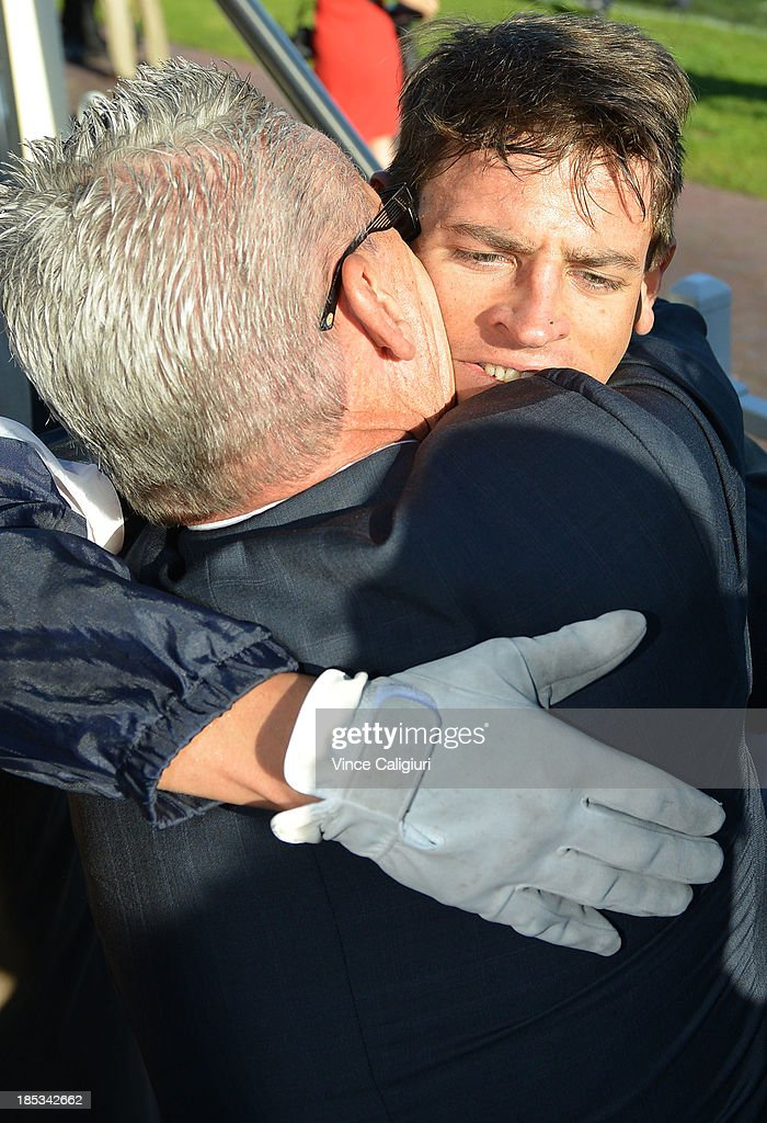 Greg Hall hugs his son Nicholas Hall after he rode Fawkner to win the BMW Caulfield Cup during Caulfield Cup day at Caulfield Racecourse on October 19, 2013 in Melbourne, Australia.