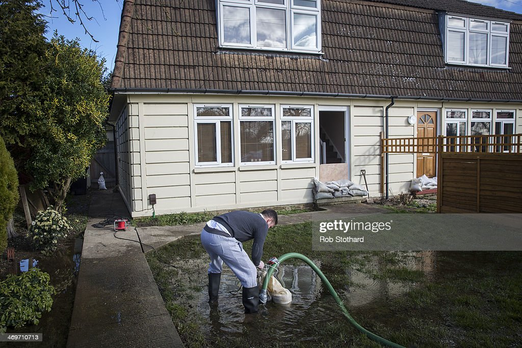 Greg Healy adjusts a pump removing ground water from his flooded garden on February 16 2014 in Staines, England. Housing near the river Thames has suffered a week of flooding after the river burst its banks on February 10, 2014.