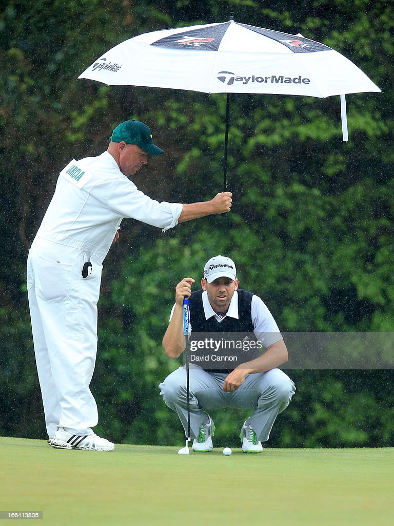 Greg Hearmon holds and umbrella for Sergio Garcia of Spain on the fifth hole during the second round of the 2013 Masters Tournament at Augusta National Golf Club on April 12, 2013 in Augusta, Georgia.