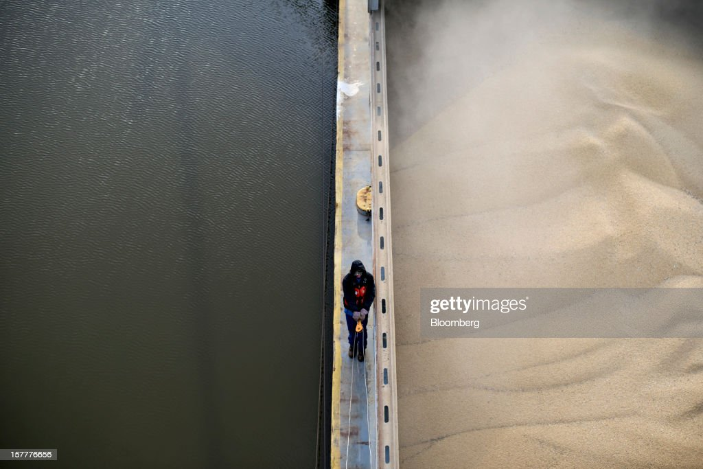 Greg Heuman pulls a cable as he prepares to close the door on a barge filled with soybeans on the Kaskaskia River, a tributary of the Mississippi River, at Gateway FS in Evansville, Illinois, U.S., on Wednesday, Dec. 5, 2012. U.S. farmers, facing aftershocks of the worst drought in 50 years, are improvising alternative plans for corn, soybeans and other grains that won't be moving to world markets as the Mississippi River dries up. Photographer: Daniel Acker/Bloomberg via Getty Images
