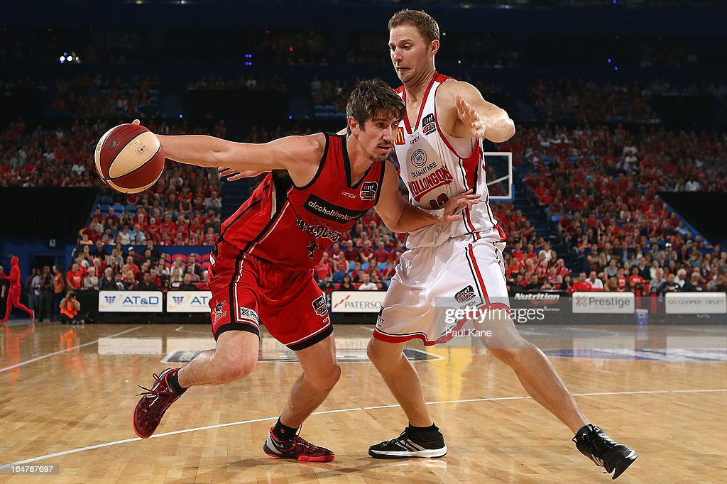 Greg Hire of the Wildcats looks to drive past Tim Coenraad of the Hawks during game one of the NBL Semi Final Series between the Perth Wildcats and the Wollongong Hawks at Perth Arena on March 28, 2013 in Perth, Australia.