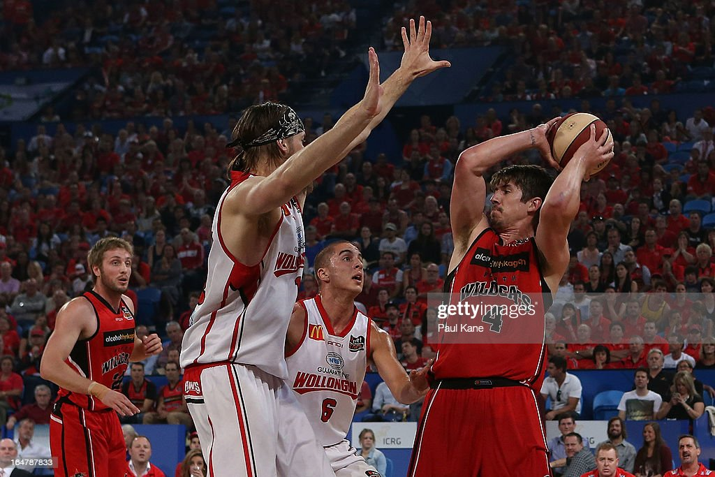 Greg Hire of the Wildcats looks to pass the ball against Larry Davidson and Mirko Djeric of the Hawks during game one of the NBL Semi Final Series between the Perth Wildcats and the Wollongong Hawks at Perth Arena on March 28, 2013 in Perth, Australia.