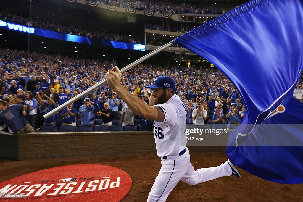 Greg Holland #56 of the Kansas City Royals celebrates with a team flag after they defeated the Oakland Athletics 9 to 8 in the 12th inning of their American League Wild Card game at Kauffman Stadium on September 30, 2014 in Kansas City, Missouri.