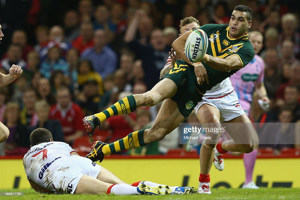 Greg Inglis of Australia passes to set up his sides first try as Kevin Sinfield (L) of England is grounded during the Rugby League World Cup Group A match between Australia and England at the Millennium Stadium on October 26, 2013 in Cardiff, Wales.