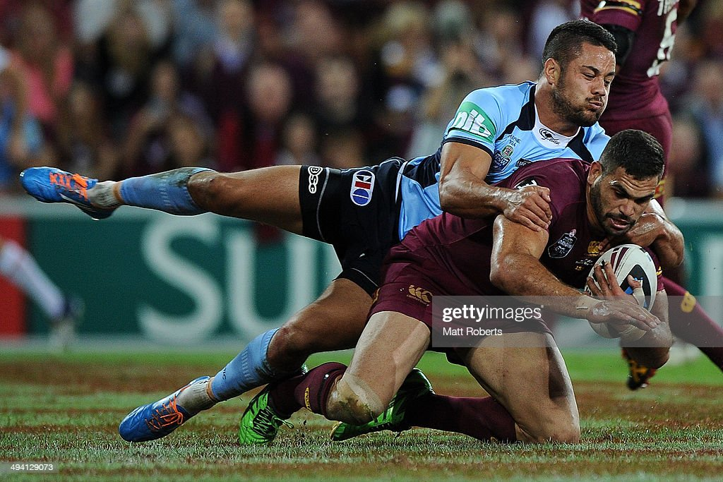Greg Inglis of the Maroons is tackled by Jarryd Hayne of the Blues during game one of the State of Origin series between the Queensland Maroons and...