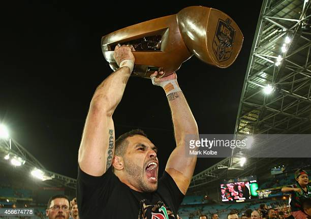 Greg Inglis of the Rabbitohs holds the trophy up to the crowd as he celebrates victory during the 2014 NRL Grand Final match between the South Sydney...