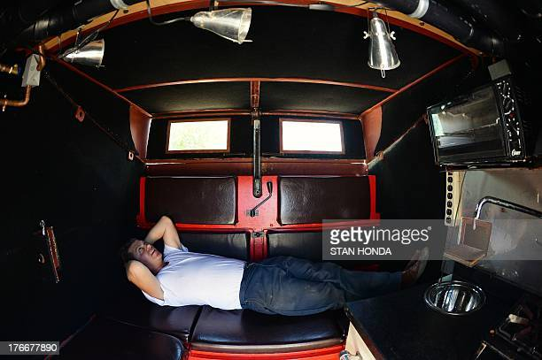 Greg Kloehn demonstrates lying inside the 'home' he made from a trash dumpster August 15 2013 in New York He bought a new dumpster for USD $1000 and...