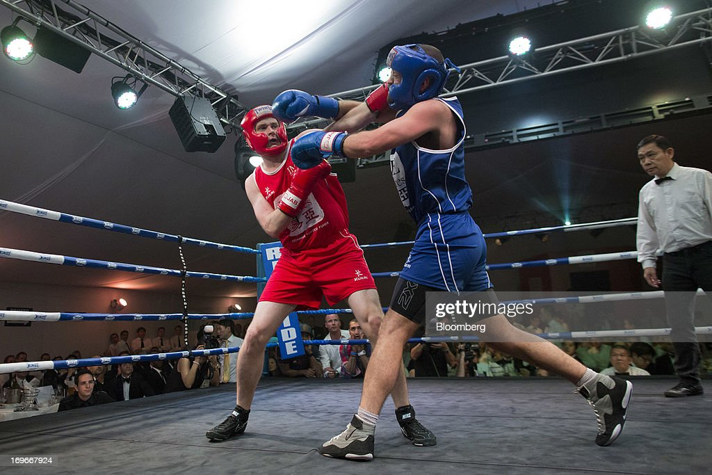Greg Lee, head of autobahn equity Asia for Deutsche Bank AG, in red, exchanges blows with Robert Nicholson, a broker at GFI Group Ltd., in the first bout during the Hedge Fund Fight Nite 2013 charity fighting event in Hong Kong, China, on Thursday, May 30, 2013. The event raises money for Operation Breakthrough and Operation Smile charities. Photographer: Jerome Favre/Bloomberg via Getty Images