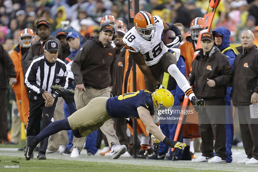 Greg Little #18 of the Cleveland Browns makes the catch and jumps over A.J. Hawk of the Green Bay Packers before going out of bounds during the third quarter at Lambeau Field on October 20, 2013 in Green Bay, Wisconsin.