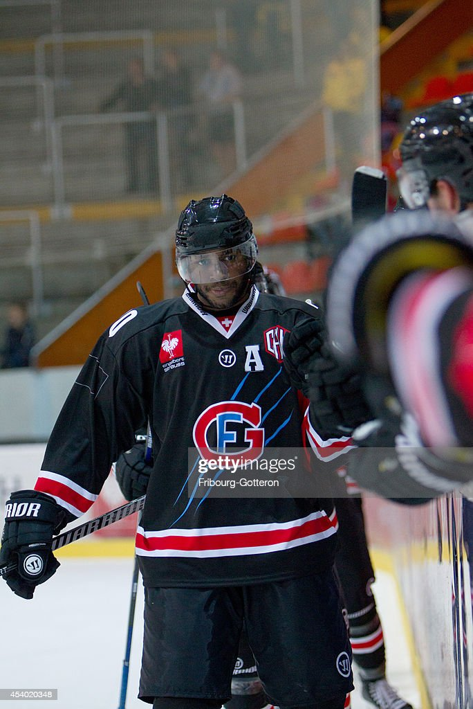 Greg Mauldin of Gotteron makes 'checks' during the group stage match between Fribourg-Gotteron and Eisbaeren Berlin on August 23, 2014 in Fribourg, Switzerland.