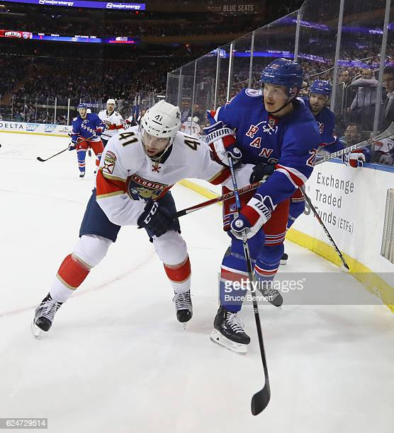 Greg McKegg of the Florida Panthers and Nick Holden of the New York Rangers battle in the corner during the first period at Madison Square Garden on...