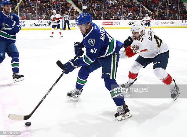 Greg McKegg of the Florida Panthers reaches around Sven Baertschi of the Vancouver Canucks during their NHL game at Rogers Arena January 20 2017 in...
