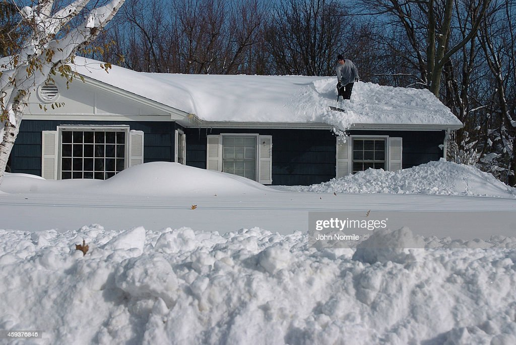 Greg Mitri shovels snow from his roofe in the Buffalo New York suburb of Lakeview November 20 2014 The record setting Lake effect snowstorm dumped up...