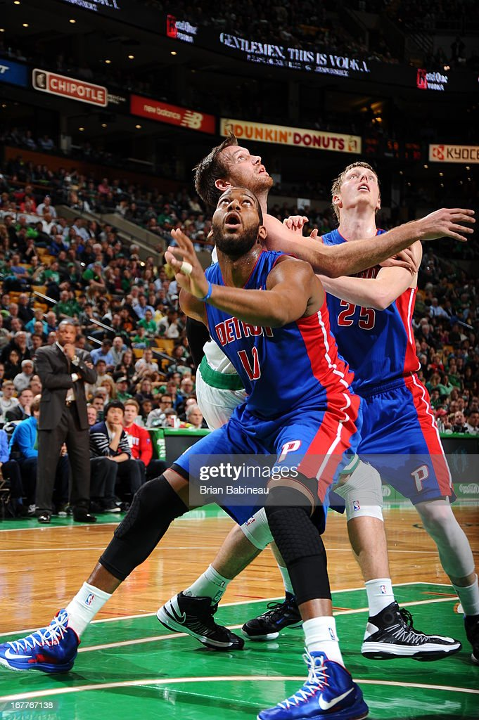 Greg Monroe #10 and Kyle Singler #25 of the Detroit Pistons battle for a rebound against Shavlik Randolph #42 of the Boston Celtics on April 3, 2013 at the TD Garden in Boston, Massachusetts.