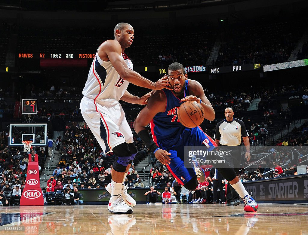 Greg Monroe #10 of the Detroit Pistons drives against Al Horford #15 of the Atlanta Hawks on December 26, 2012 at Philips Arena in Atlanta, Georgia.