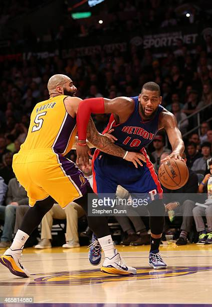 Greg Monroe of the Detroit Pistons drives against Carlos Boozer of the Los Angeles Lakers at Staples Center on March 10 2015 in Los Angeles...